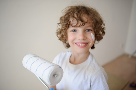 Cute little boy holding a roller for painting. His cheek was smeared with white paint. A boy with a cheerful smile, looking into the camera. Against the background of a white wall. Stock Photo