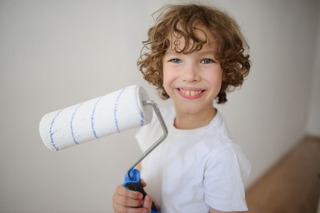 lad: Cheerful boy with a roller to paint in his hands. Curly lad 8-9 years, standing near a white wall. He looks at the camera with a smile.