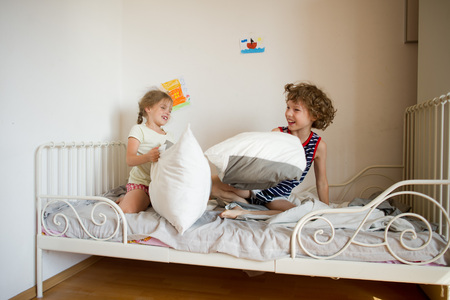 uncombed: Little brother and sister staged a pillow fight in the bedroom. They sit on a bed in pajamas. Children hair uncombed. Happy smiles on their faces.