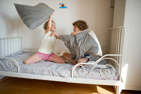 Little brother and sister staged a pillow fight on the bed in the bedroom. Naughty children beat each other pillows. They like that kind of game.