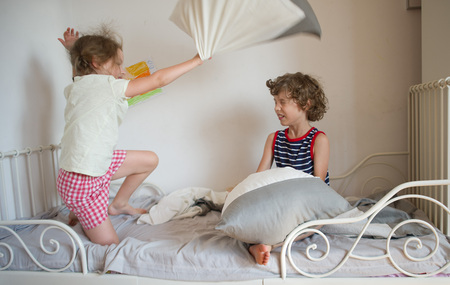 brother sister fight: The brother and the sister have arranged fight by pillows on a bed in a bedroom. The naughty little girl beats the brother a pillow. The boy has closed eyes. Children love this game.