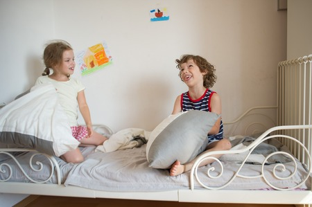 hassle: Brother and sister sit on the bed in the bedroom. They fight pillows. Boy make face. Children love this game. On a white wall bright childrens drawings. Stock Photo