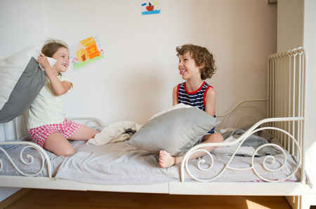 brother sister fight: Brother and sister sit on the bed in the bedroom. They fight pillows. Boy make face. Children love this game. On a white wall bright childrens drawings. Stock Photo
