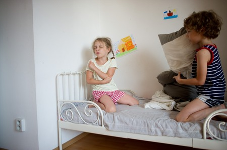 brother sister fight: Brother and sister fight pillows on the bed in the bedroom. Girl hurt, she is offended. The boy looks at her sister. On the white wall of bright childrens drawings