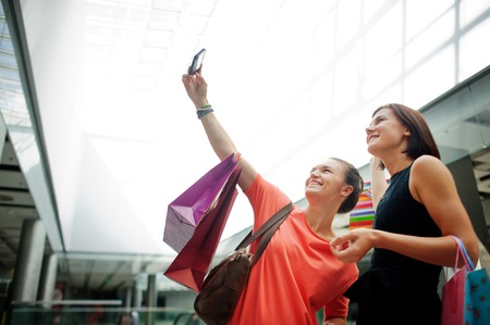 cute girlfriends: Two cute girlfriends make selfie at the mall. In the hands of one of the girls cell phone. They are posing and laughing. Stock Photo