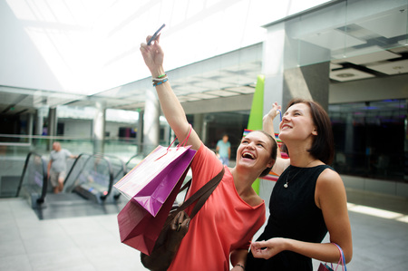 cute girlfriends: Two cute girlfriends make selfie at the Mall. In the hands of one of the girls cell phone. They are posing and laughing.