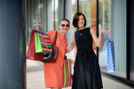 cheerfully: Beautiful young women show bright multi-coloured packages with purchases. They look into a camera and cheerfully smile. Girlfriends have fine mood after shopping.