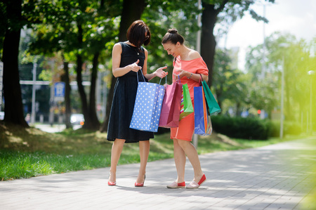 cute girlfriends: Cute girlfriends share their impressions after shopping. Girls show each other the contents of packages. They have wonderful mood.