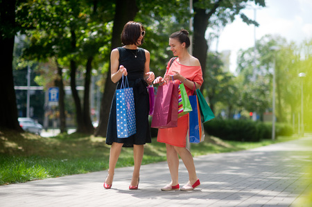 Two girlfriends share their impressions after shopping. Beautiful girls with colorful packages in their hands. They have wonderful mood.