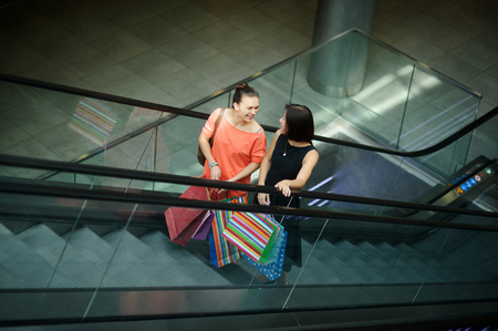 stylishly: Two young women on the escalator at the Mall. They share their impressions and smiling. Girlfriends are stylishly dressed. In hands multicoloured packages with purchases.