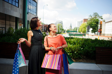 cute girlfriends: Young women with bright bags in their hands. Two cute girlfriends stand in the courtyard of the shopping center. They looking somewhere up. On the faces of the women smile.