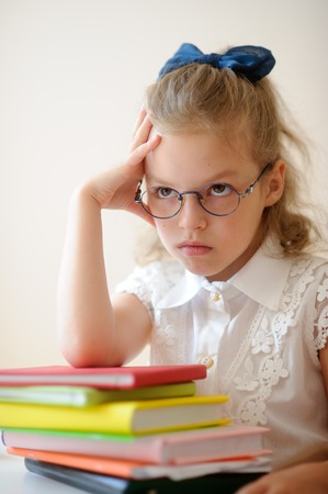 studious: Cute little schoolgirl pondered. Girl in glasses sits leaning on a stack of books. She had a serious expression on his face.