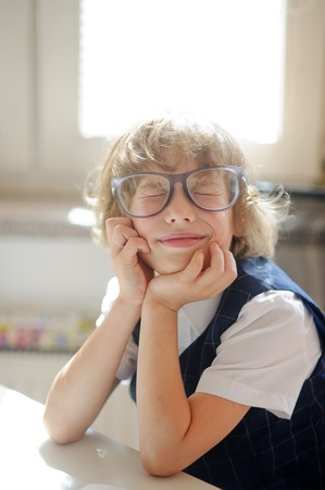 Funny little schoolboy in huge glasses has fallen into a reverie. The child propped head in his hands and closed his eyes. It is a disciple of an elementary school. Back to school.