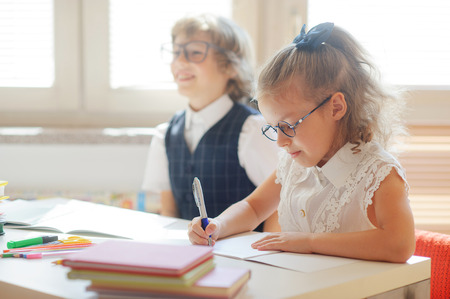 Disciples of an elementary school are sitting at the same desk. Cute schoolgirl writing something. Funny boy in glasses sitting next. On the desk in children are school supplies and textbooks. Stock Photo
