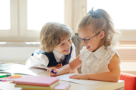 neighbor: Two little classmate, laddie and girlie, are sitting at the same desk. Cute schoolgirl with glasses writes something. The neighbor on a school desk looks at the girlie. Back to school.