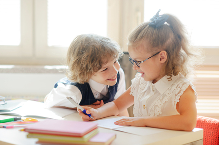 girlie: Two little classmate, laddie and girlie, are sitting at the same desk. Children learn in elementary school. Cute schoolgirl with glasses writes something. Neighbor on a school desk looks at the girl.