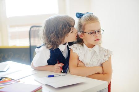 žák: Žáci ze základní školy sedí u jednoho stolu. Roztomilá žákem rozzlobená. Chlapec něco šeptá do ucha. Na školním stole mají děti školní příslušenství. Zpátky do školy. Reklamní fotografie