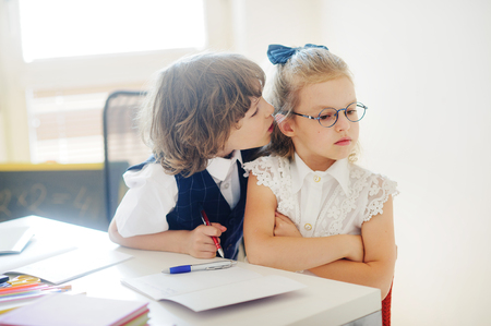 Primary school pupils sit at one desk. Cute schoolgirl angry. The boy whispers something in her ear. On a school desk children have school accessories. Back to school.