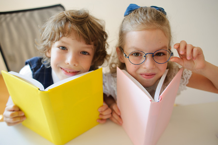 Two young classmate, boy and girl, are sitting at the same desk. Children learn in elementary school. In the hands of the students open textbooks. Kids fun look into the camera. Back to school. Stock Photo
