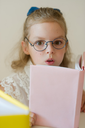 bespectacled: Lovely small student reads. Schoolgirl bespectacled holds the textbook. She has serious look. Stock Photo