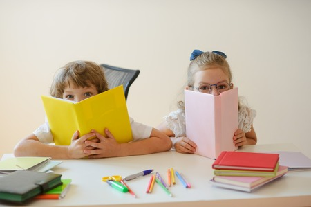 Two young classmate, boy and girl, are sitting at the same desk. Children learn in elementary school. In the hands of the students open textbooks. Kids fun look into the camera. Back to school. Reklamní fotografie