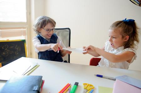 niños actuando: divertidos pequeños alumnos se sientan en un escritorio. Son alumnos de una escuela primaria. Niño y la niña están actuando. diversión niños. En una escuela de niños de escritorio tienen accesorios de la escuela y los libros de texto. De vuelta a la escuela.