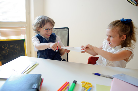 ni�os actuando: Funny little pupils sit at one desk. They are pupils of an elementary school. Boy and girl are acting up. Kids fun. On a school desk children have school accessories and textbooks. Back to school. Foto de archivo