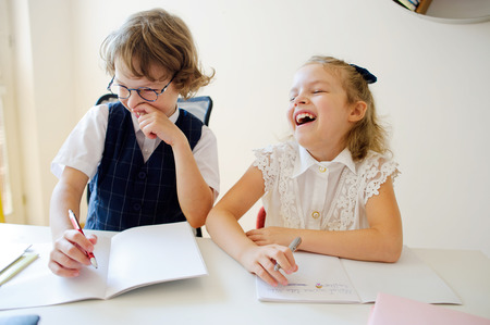 bespectacled man: Primary school pupils are sitting at the same desk. Little pupils something to write in their copybooks. Children are very fun, they laugh. On the desk in children are school supplies and textbooks.