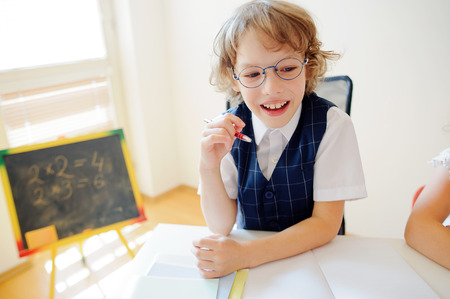 bespectacled: Cheerful little student bespectacled sits at school desk. It is a disciple of an elementary school. In a hand at boy ball pen. On a school desk copybooks lay. Near to a school desk a small blackboard.