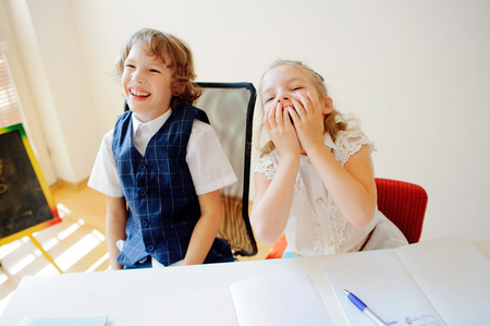 bespectacled man: Funny little schoolchildren, boy and girl, sit at one desk. Its elementary school students. Children laugh. On the desk in children are school supplies and textbooks. Back to school.
