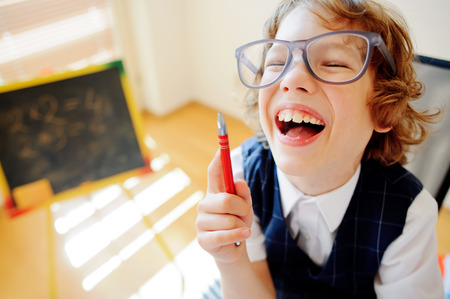 scholastic: Cheerful little student bespectacled sits at school desk. It is a disciple of an elementary school. In a hand at boy ball pen. On a school desk copybooks lay. Near to a school desk a small blackboard.