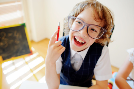 bespectacled: Funny little student bespectacled sits at school desk. It is a disciple of an elementary school. In a hand at boy ball pen. On a school desk copybooks lay. Near to a school desk a small blackboard. Stock Photo