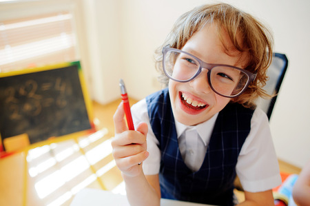 Funny little schoolboy in glasses sits at a school desk. It is a disciple of an elementary school. In a hand at boy ball pen. On a school desk copybooks lay. Near to a school desk a small blackboard.