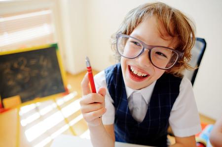 Legrační malý školák v brýlích sedí u školního stolu. Je to žák základní školy. V ruce na chlapecké kuličkové pero. Na školní desce leželo učebnice. V blízkosti školního stolu je malá tabule. Reklamní fotografie