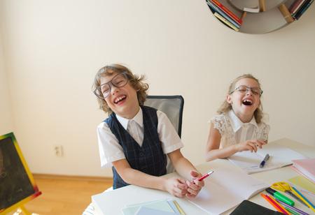Discepoli di una scuola elementare, ragazzo e ragazza, sono seduti allo stesso tavolo. I bambini sono molto divertenti, ridono. Sulla scrivania nei bambini sono materiale scolastico e libri di testo. Ritorno a scuola. Archivio Fotografico