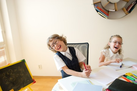 bespectacled man: Disciples of an elementary school, boy and girl, are sitting at the same desk. Children are very fun, they laugh. On the desk in children are school supplies and textbooks. Back to school. Stock Photo