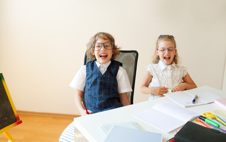 bespectacled: Ridiculous little students bespectacled, boy and girl, share the same desk. They are pupils of an elementary school. They laugh. On the desk in children are school supplies and books. Back to school Stock Photo