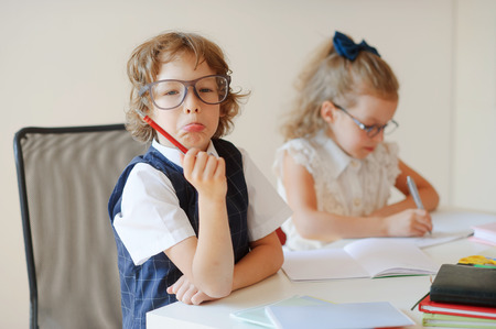 girlie: Funny little pupils sit at one desk. They are pupils of an elementary school. Boy fools around, girlie writes something with a serious look. On a school desk children have school accessories and textbooks. Stock Photo