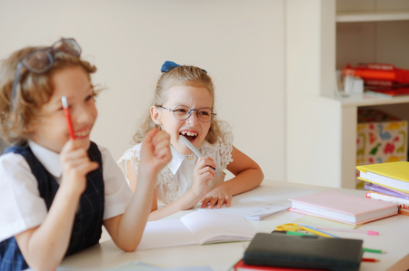 bespectacled man: Funny little pupils sit at one desk. They are pupils of an elementary school. Boy and girl laugh. On a school desk children have school accessories and textbooks. Back to school.