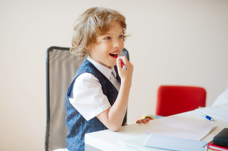 reverie: Cute little schoolboy sitting at a school desk with dreaming views. A boy looking somewhere to the side. On a school desk there are school accessories and copybooks. This elementary school student. Stock Photo