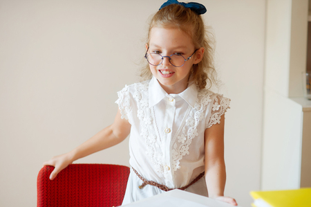 girlie: Cute little schoolgirl stands near desks. The girlie has a good mood. She smiles.