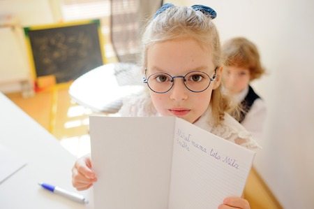 Cute little schoolgirl in glasses shows her copybook. Girl diligently wrote a few words. She is elementary school student. Stock Photo