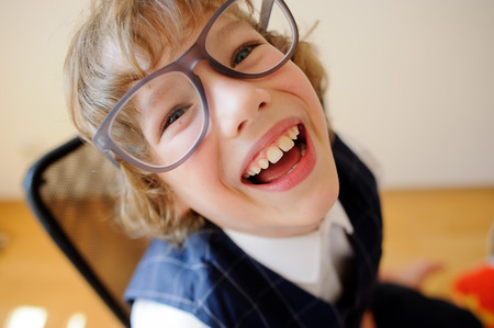 žák: Little cheerful schoolboy. Curly boy in huge glasses light-heartedly laughs. It is a disciple of an elementary school.