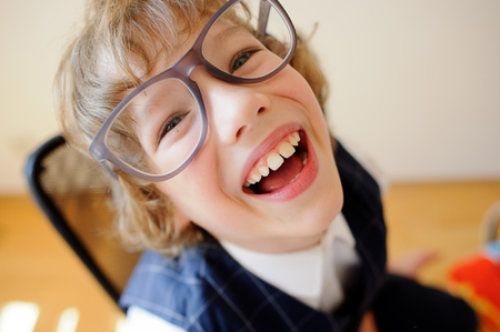 kinky: Funny little schoolboy. Kinky boy in huge glasses carefree laughs. He has a good mood. This is a primary school pupil.