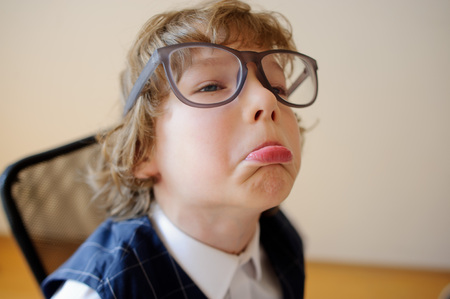 The ridiculous small schoolboy in huge glasses make faces. He has a great mood. This elementary school student.