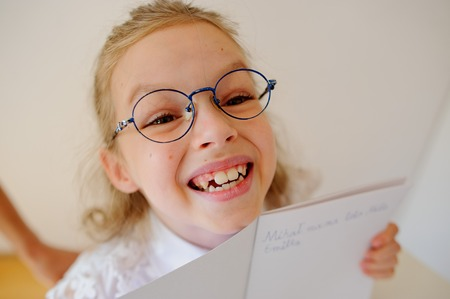diligent: Cute little schoolgirl in glasses shows her copybook. Girl diligently wrote a few words. She is elementary school student. Stock Photo