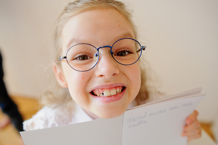 wrote: Cute little schoolgirl in glasses shows her copybook. Girl diligently wrote a few words. She is elementary school student. Stock Photo