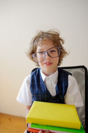 Disheveled little schoolboy holding a stack of textbooks and smiles. He has a great mood. Huge glasses fall from his face. It is a disciple of an elementary school.