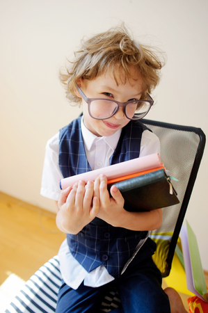 žák: Neupravený malý školák drží hromadu učebnic a úsměvů. Má výbornou náladu. Obrovské brýle spadnout z tváře. Je žákem základní školy.