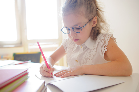 Cute little schoolgirl in glasses something diligently writes in a notebook. Girl sitting at the desk in the classroom. She is elementary school student. Stock Photo